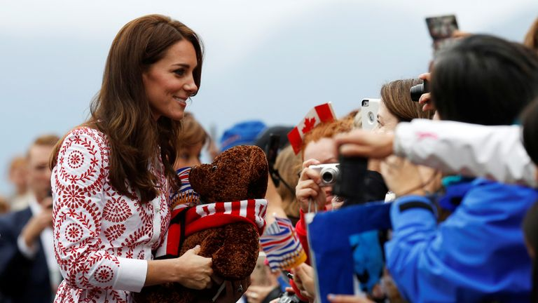 The Duchess of Cambridge carries a stuffed bear she received while greeting people at Jack Poole Plaza in Vancouver, British Columbia