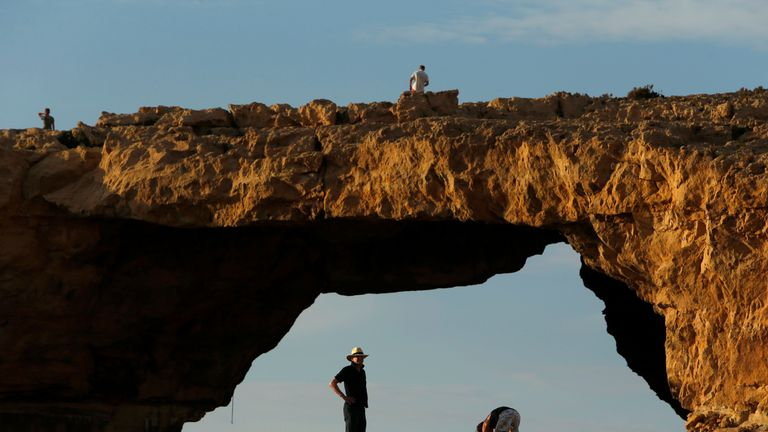 Tourists walk near the Azure Window, a 50m high rock arch, at Dwejra Point cliffs on the Maltese island of Gozo. The arch is in danger of collapse due to erosion