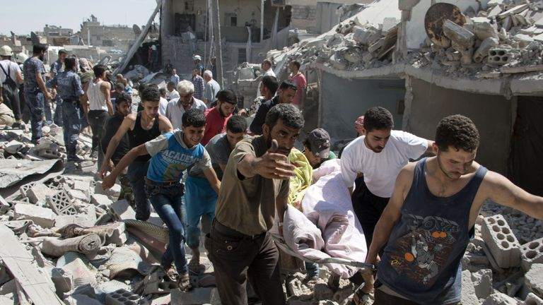 People carry someone on a stretcher after a missile strike in Maghayir district in Aleppo in 2015