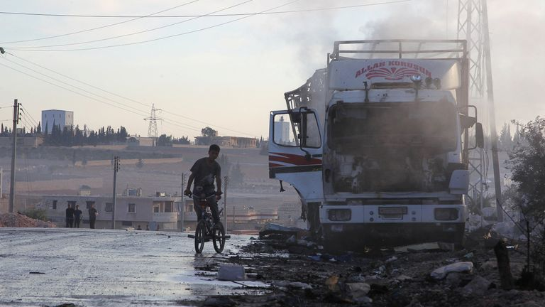 A boy rides a bicycle near a damaged aid truck after an airstrike