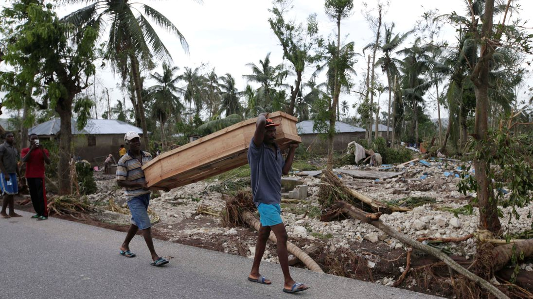 Men carry a coffin after Hurricane Matthew hit Cavaillon, Haiti