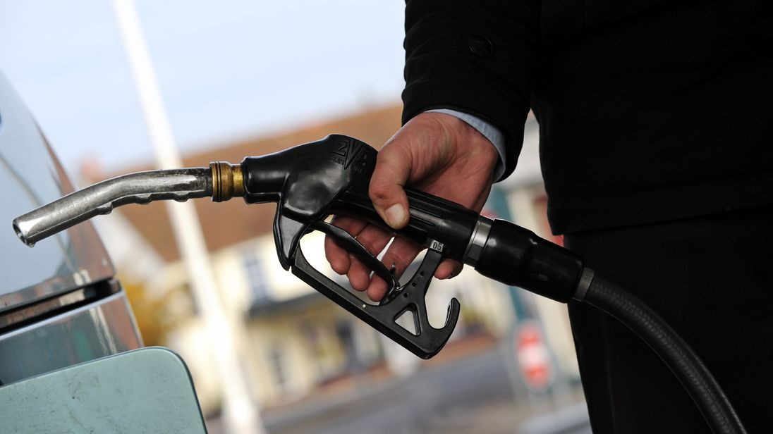 A customer pulls the nozzle of a petrol pump from their car