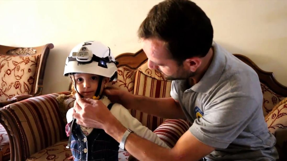 A Syrian White Helmet rescuer and his son