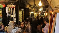 People shop at the main market, or souk, in the Syrian city of Aleppo June 23, 2010.