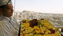 A chef displays a collection of dessert fruits with the historic city of Aleppo in the background October 21, 2007