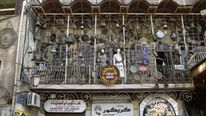 Tourists walk past a trinkets shop in the Jdeideh district of the northern Syrian city of Aleppo June 23, 2010.