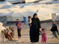 A woman walks with children at a refugee camp housing Iraqi families who fled fighting in the Mosul area in the northeastern town of al-Hol in Syria's Hasakeh province