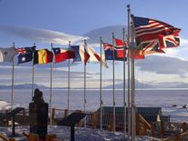 MCMURDO STATION, ANTARCTICA - OCTOBER 21: Flags of the original 12 signatory nations of the Antarctic Treaty fly next to a bust of Admiral Richard Byrd at McMurdo Station on October 21, 2005 in Antartica. (Photo by Rob Jones/National Science Foundation via Getty images)