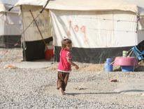 A displaced child who fled Islamic State militants from Mosul plays at Deepaka camp in the northwest of Erbil