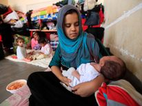 A displaced woman who fled from Islamic State militants in Mosul holds her baby at Deepaka camp in the northwest of Erbil