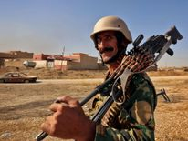 An Iraqi Kurdish Peshmerga fighter looks on in Nawran village