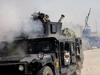 An Iraqi special forces soldier fires a cannon at Islamic States fighters in Bartella