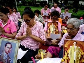 Well-wishers hold pictures of Bhumibol Adulyadej as they pray for him.