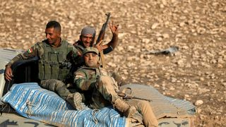 Peshmerga forces sit in the back of a vehicle in the east of Mosul