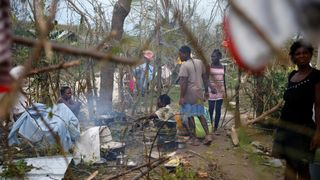 People cook next to fallen trees after Hurricane Matthew passes Jeremie, Haiti