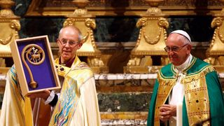 Justin Welby displays a gift given by the Pope during his vist