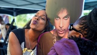 Trena lawson of Hermosa Beach CA, poses next to a life size cut-out of Prince