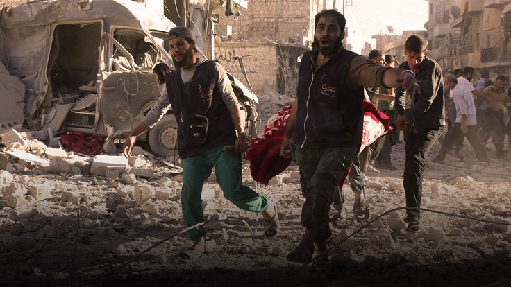 Residents of Aleppo carrying someone from the rubble