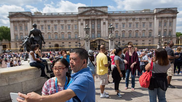 Tourists take pictures outside Buckingham Palace