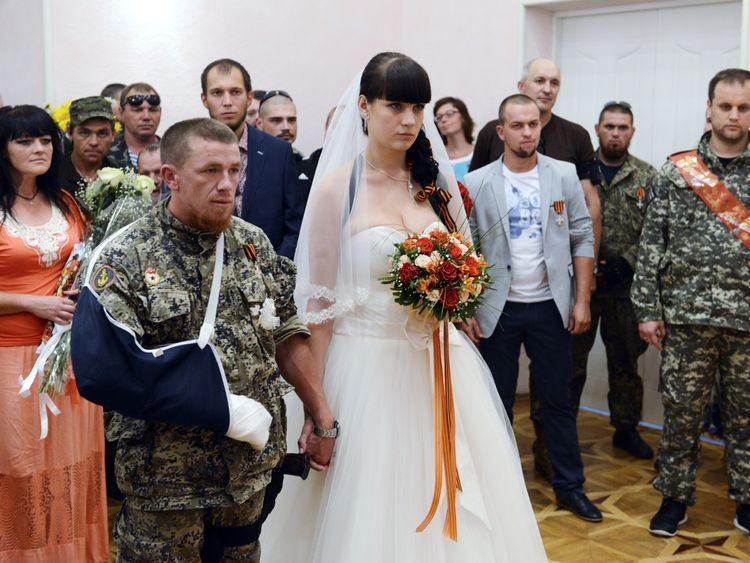 Arsen Pavlov (L), a field commander of the so called 'Donetsk People's Republic', and his bride Elena Kolenkina (C), stand during their wedding ceremony in Donetsk on July 11, 2014.