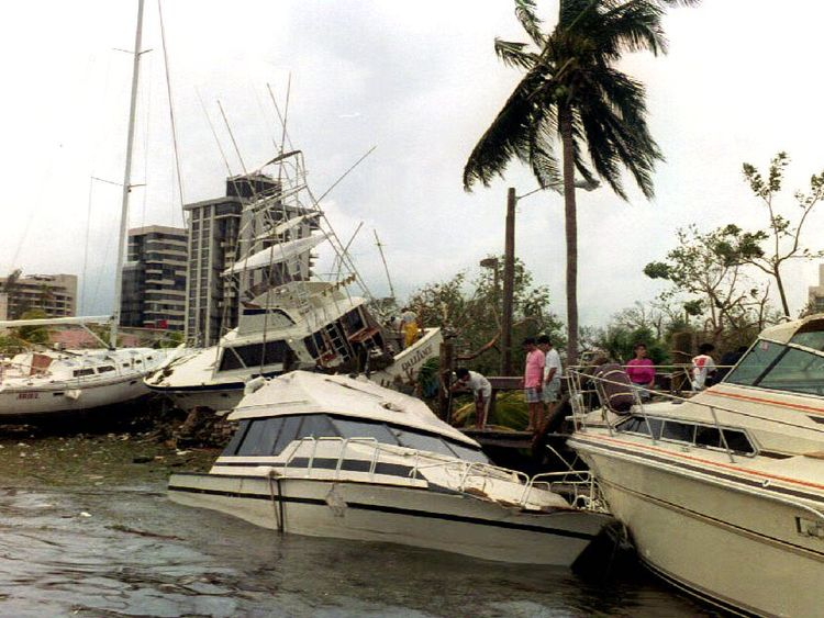MIAMI, FL - AUGUST 24: Wrecked boats sit on the sea wall 24 August 1992 at the docks at Dinner Key in the Coconut Grove area of the city after Hurricane Andrew passed through southern Florida. Andrew was the strongest hurricane to hit southern Florida in 40 years. (Photo credit should read ROBERT SULLIVAN/AFP/Getty Images)