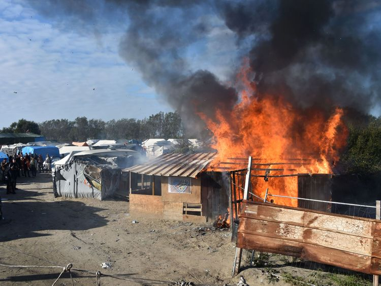 A shack is set on fire during the demolition