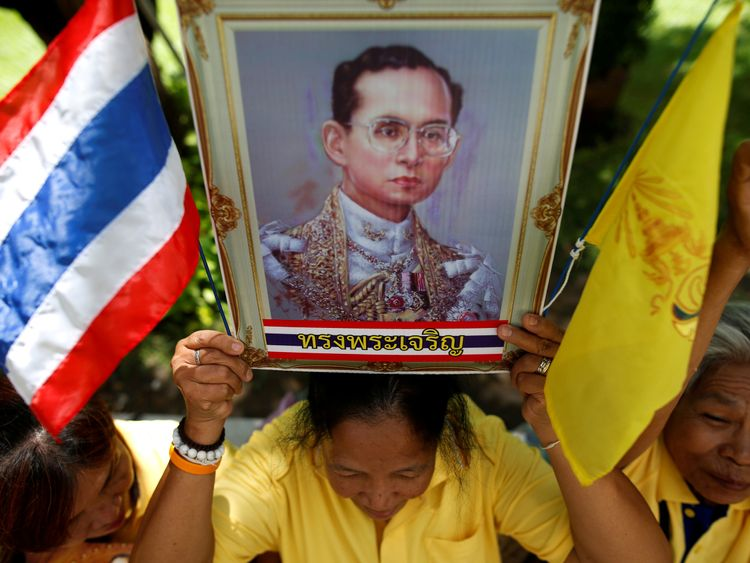 A well-wisher holds a picture of King Bhumibol Adulyadej at Siriraj hospital