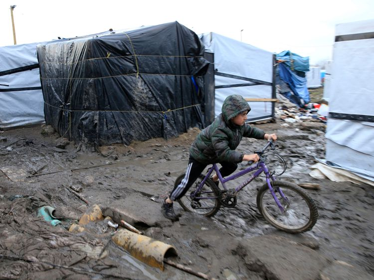 """A young boy from Afghanistan pushes his bycicle in the mud in the southern part of the camp known as the """"Jungle"""", a squalid sprawling camp in Calais, northern France, February 25, 2016. A French judge on Thursday upheld a government plan to partially demolish a shanty town for migrants trying to reach Britain on the outskirts of the northern port of Calais, an official spokesman said. REUTERS/Pascal Rossignol"""