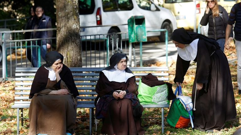 Nuns rest on a bench after been evacuated from their monastery