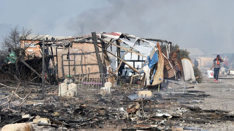 A migrant walks past a makeshift shelter destroyed by a fire
