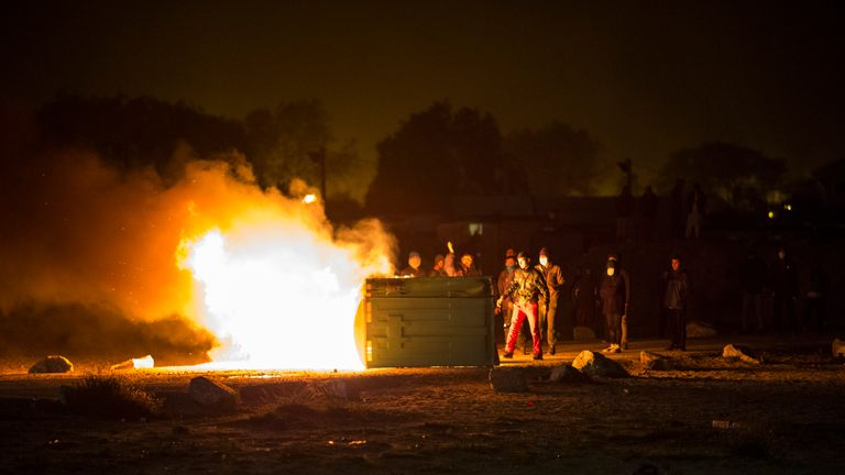 A portable chemical toilet burns as migrants clash with French riot police