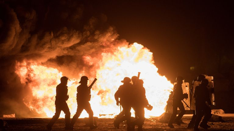 French riot police advance through tear gas and smoke in the Jungle refugee camp