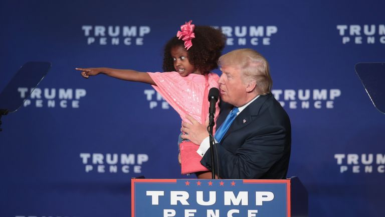 A young Trump fan points out her parents to presidential candidate Donald Trump