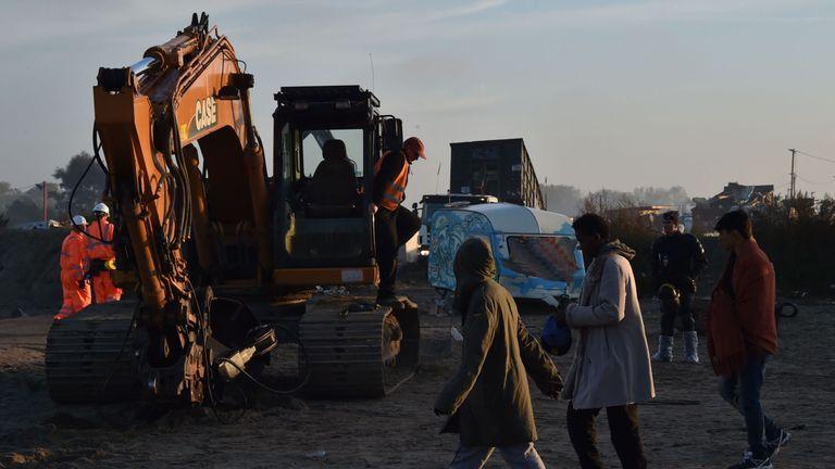 Migrants walk past excavators being used by a demolition crew