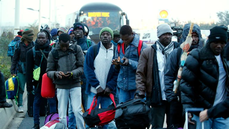 Migrants with their belongings queue near buses