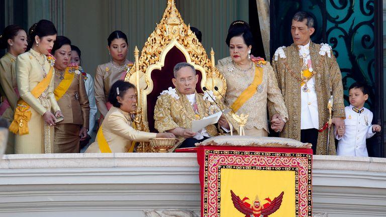 Princess Maha Chakri Sirindhorn assists King Bhumibol Adulyadej as he delivers his birthday speech in 2011