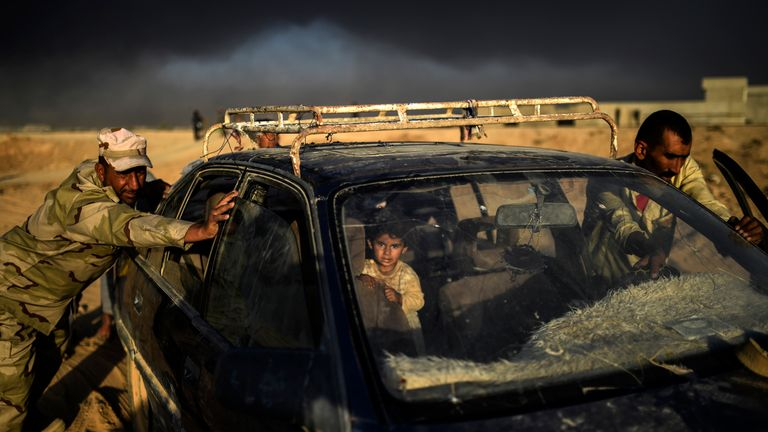 TOPSHOT - An Iraqi forces member helps a displaced man push a car as they arrive at refugee camp on October 22, 2016 in the town of Qayyarah, south of Mosul, as an operation to recapture the city of Mosul from the Islamic State group takes place. Iraqi security forces battled for a second day with Islamic State group gunmen who infiltrated Kirkuk in a brazen raid that rattled Iraq as it ramped up an offensive to retake Mosul