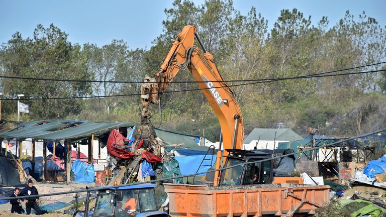 An excavator tears down a makeshift shelter