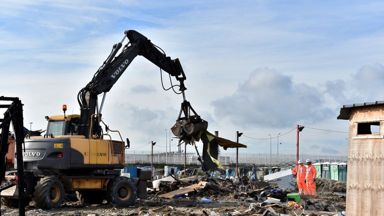 Two members of the demolition crew stand in front of an excavator