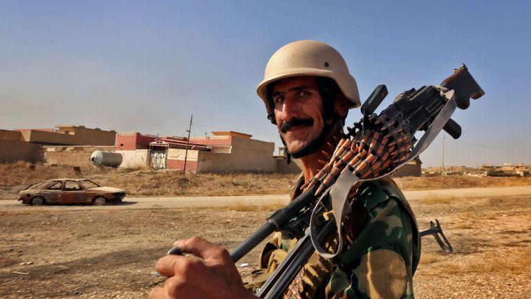 An Iraqi Kurdish Peshmerga fighter looks on in Nawran village
