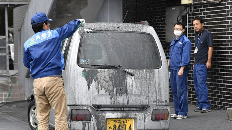 DATE IMPORTED:08 October, 2016An officer of the city government cleans a car covered in volcanic ash which came from the eruptive crater of Mount Aso in Aso, Kumamoto prefecture, southwestern Japan, in this photo taken by Kyodo October 8, 2016. Mandatory credit Kyodo/via REUTERS ATTENTION EDITORS - THIS IMAGE WAS PROVIDED BY A THIRD PARTY. EDITORIAL USE ONLY. MANDATORY CREDIT. JAPAN OUT. NO COMMERCIAL OR EDITORIAL SALES IN JAPAN.