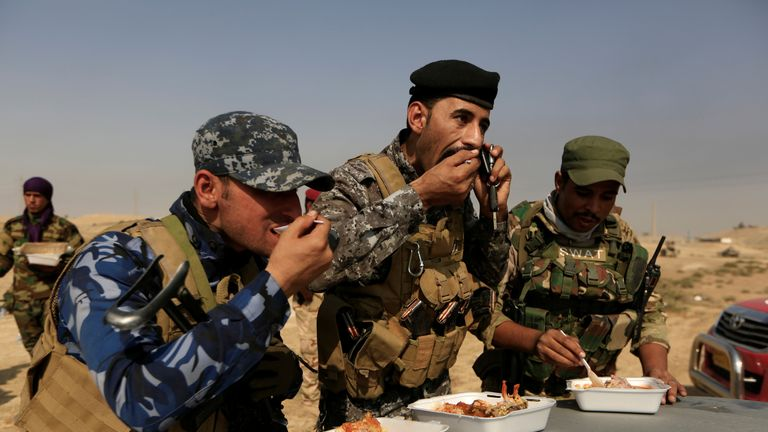 Members of Iraqi forces eat their lunch in front of Islamic States positions at the town of Safayah near Mosul