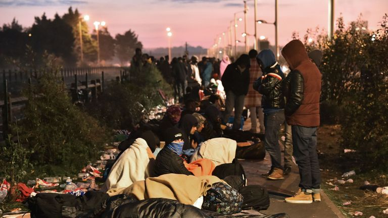 Migrants sleep at the end of the queue for an aid station