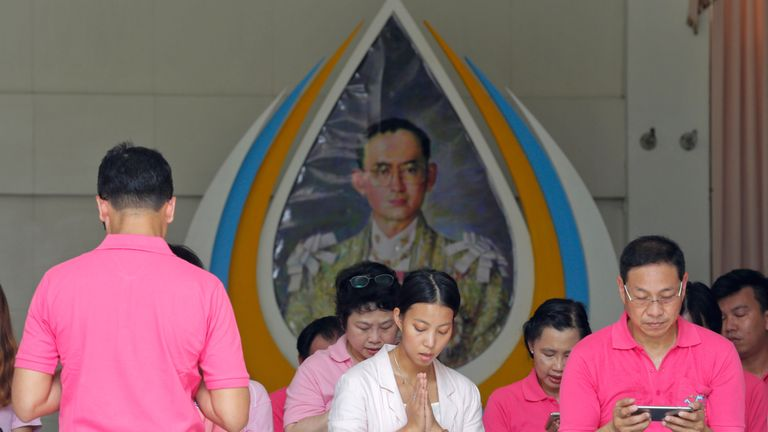 Crowds wear symbolic pink in front of a picture of the King