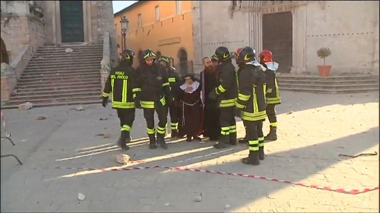 Rescue workers help a nun in Piazza San Benedetto in Norcia