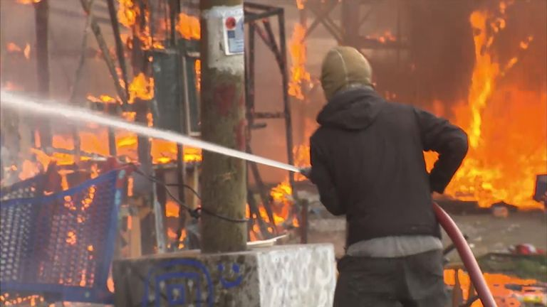 Volunteer firefighters attempt to extinguish blazing migrant camp in Calais