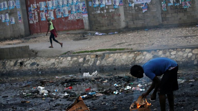 A man warms himself next to a fire in Cite-Soleil in Port-au-Prince, Haiti