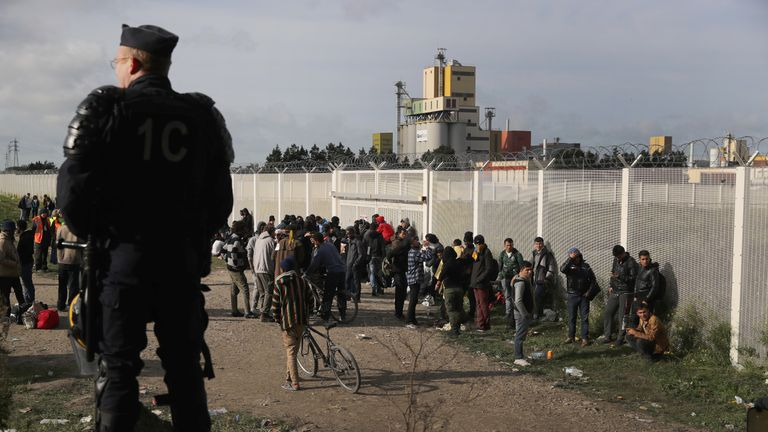 Migrants wait for transport outside the camp