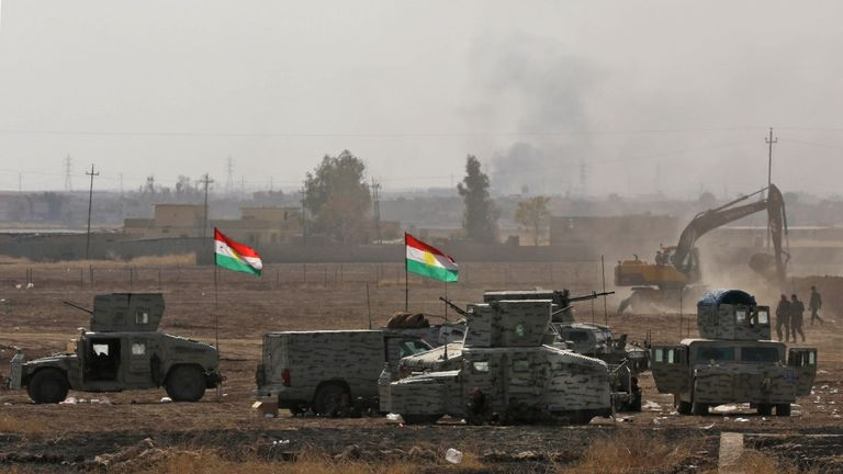 Iraqi Kurdish Peshmerga fighters and Iraqi forces about 22 miles east of Mosul, with a digger in the distance