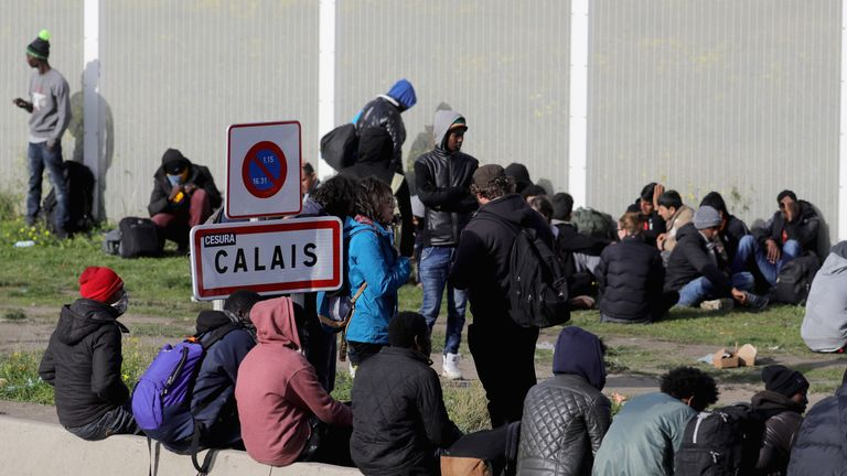 Migrants wait for transport outside the 'Jungle'